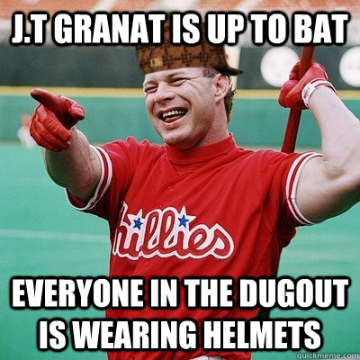 J.t granat is up to bat everyone in the dugout is wearing helmets