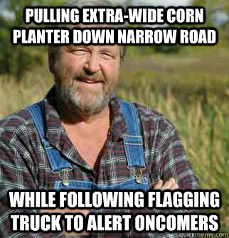 Pulling Extra-wide corn planter down narrow road While following flagging truck to alert oncomers