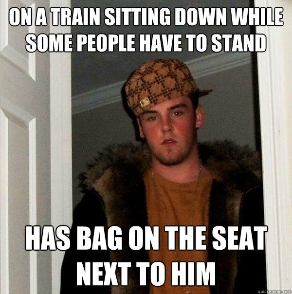 On a train sitting down while some people have to stand Has bag on the seat next to him