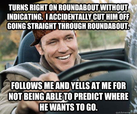 Turns right on roundabout without indicating.  I accidentally cut him off going straight through roundabout. Follows me and Yells at me for not being able to predict where he wants to go. - Turns right on roundabout without indicating.  I accidentally cut him off going straight through roundabout. Follows me and Yells at me for not being able to predict where he wants to go.  SCUMBAG DRIVER