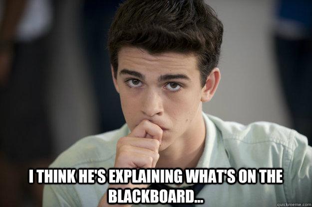 I think he's explaining what's on the blackboard...
